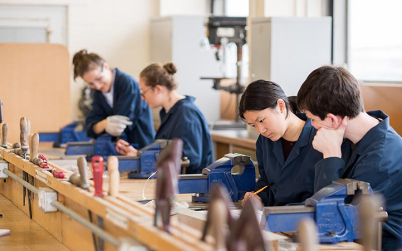 Four students in a class looking at work